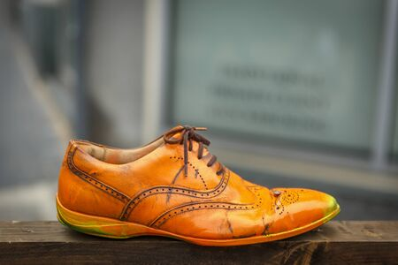 An old abandoned orange shoe on a wooden plank Stock Photo
