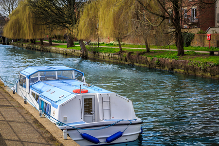trip over: View from behind of a boat on a river, in the middle of a natural landscape in Norwich, UK