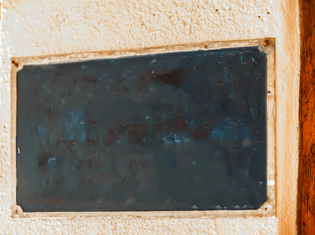 Old and deteriorated dark colored poster, anchored to a wall Stock Photo