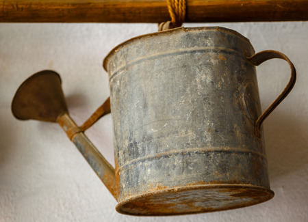 cabine de douche: Old metallic watering can, hung from a stick on a white wall