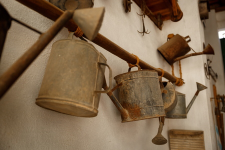 Several old metal showers, hanging from a stick on a wall Stock Photo