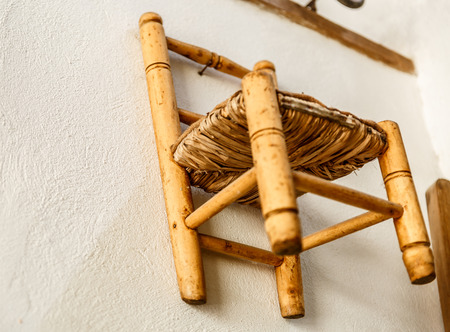 Small old wicker and wood chair, hung on a white wall