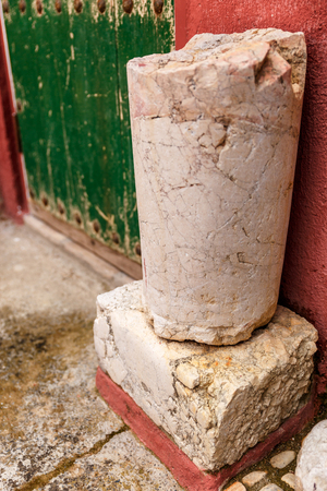 outworn: Small ruins of an old stone structure, next to the door of an old house