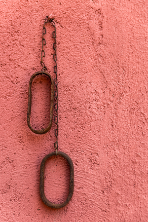 Old rusty metal chain hanging on a red and rough wall