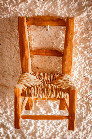 Antique wicker and wood chair, hung from a rugged white wall