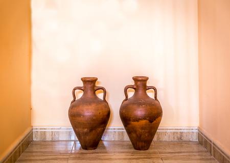 Dos ánforas decorativas de color marrón en un rincón Foto de archivo