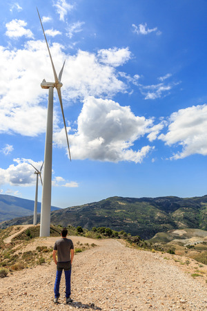 Man looking at two windmills for electric power creation, in a Spanish landscape