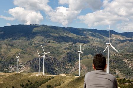 Mann, der eine große Landschaft mit Windmühlen im Hintergrund genießen Standard-Bild - 69799680