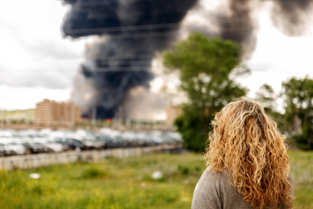 A huge and dangerous fire in the midst of a large population, is witnessed by a woman Stock Photo