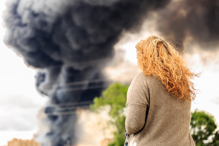 Woman looking at a huge and thick smoke from a big fire Stock Photo