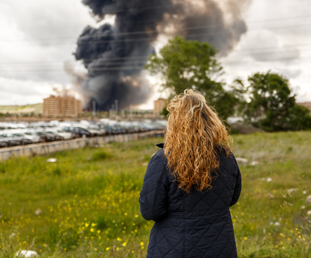 Expectant woman watching a large fire in a population