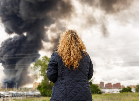 A woman observes a large thick smoke from a fire
