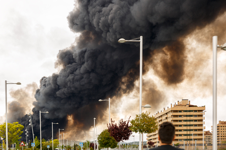 A man observes a dense and dark smoke from a fire, covering the sky of a population Stock Photo