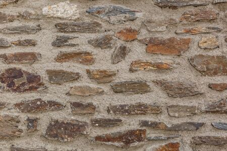 brawn: Brown wall background made of solid stones and cement