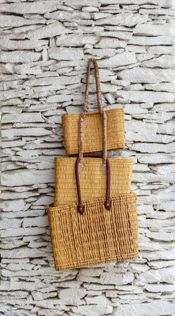 basketry: Three wicker bags hanging on a rugged and white wall Stock Photo