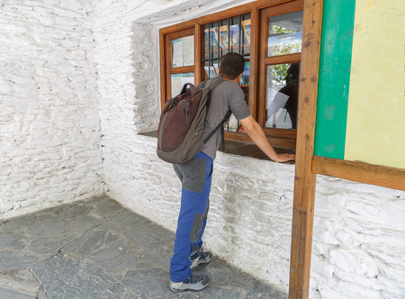 waits: A traveler with a backpack waits for information in a small tourist office