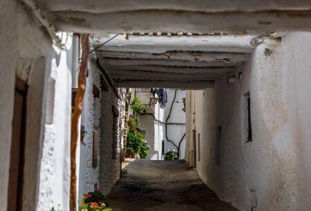 Beautiful view of a narrow street in a village of La Alpujarra, Granada, Spain