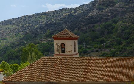 View of the bell tower and roof of a beautiful church in La Alpujarra, Granada, Spain Stock Photo