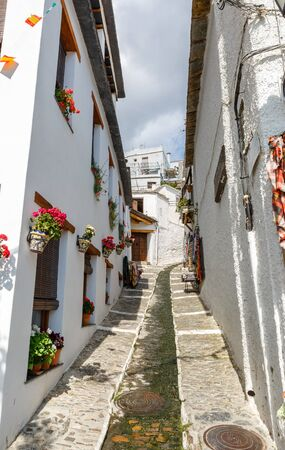 alpujarra: Large and narrow street with a water channel in the middle, in a village of La Alpujarra, Granada, Spain