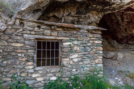 eyes cave: Entrance of a cave next to an old stone house Stock Photo
