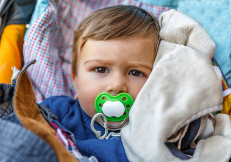 A lovely child with pacifier in the baby carriage