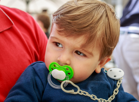 A cute little boy with pacifier, in the arms of an adult