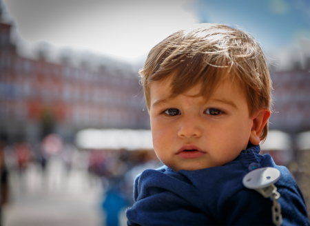slight: A cute child looks very serious towards the front