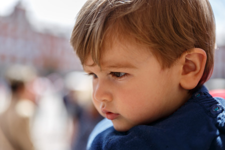 A cute and serious child looking intently, in the middle of a street