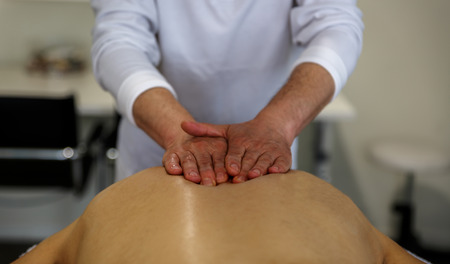 An experienced masseuse applies his hands on the back of a patient