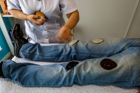 女性セラピストが担架に横たわっている患者の磁石療法