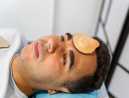 A patient lying down and relaxed on a stretcher with a magnet on his forehead