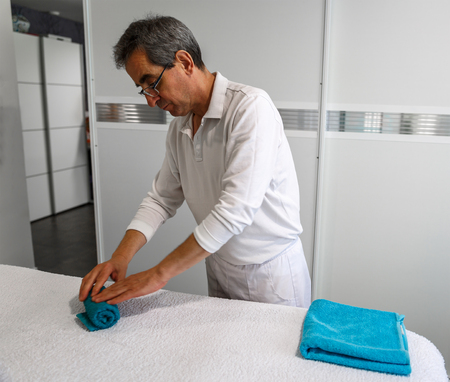 A mature therapist rolls towels on a white stretcher
