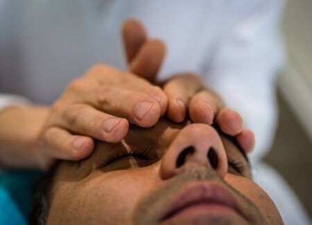 A therapist puts his hands on a patients forehead