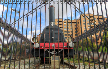 View of the front of an old train, behind bars