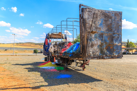View from behind of a burnt and colorful trailer, on a summer day