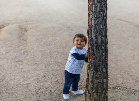 A small child grabs a tree to keep from falling