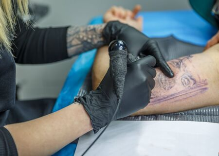 Blonde woman sketches a tattoo with her tattoo machine on a mans arm Stock Photo
