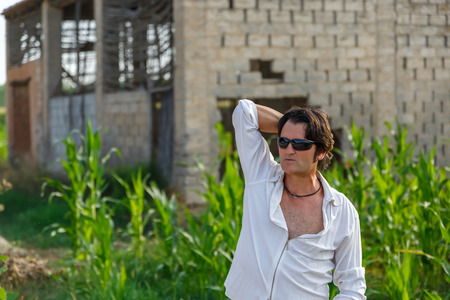 contemplates: A mature man with an abandoned house behind, contemplates nature on a summer day