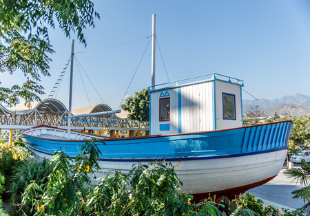 nerja: Side view of a small boat of white and blue colors on a bright day Stock Photo