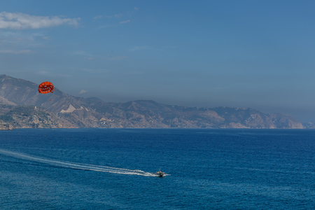 nerja: Mediterranean coastal landscape with a speedboat doing sport, on a summer day