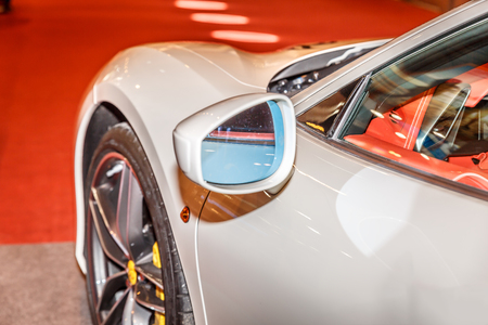 alloy: View of rearview mirror and tire, of a white sports car in a showroom