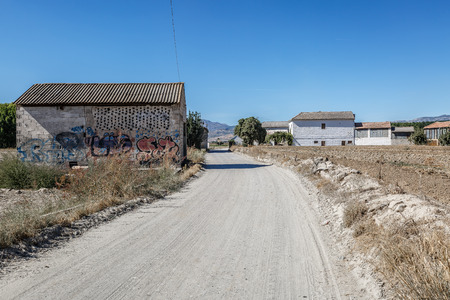 Old unpaved road in the middle of a small and arid population Editorial