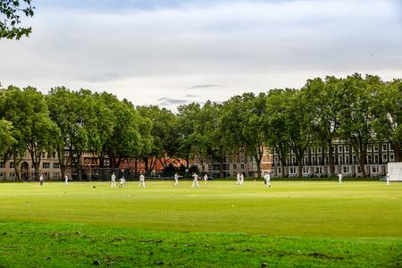 Hombres jugando al cricket en un gran parque verde en una zona residencial de Londres, Reino Unido Foto de archivo