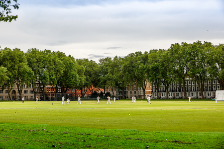 Men playing cricket in a large green park in a residential area of london, UK