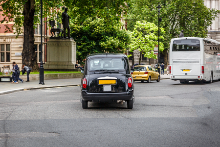 hackney carriage: View of a London street with a black taxi in the middle, United Kingdom