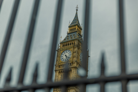 Special view of the Big Ben tower seen behind bars on a dark day, United Kingdom
