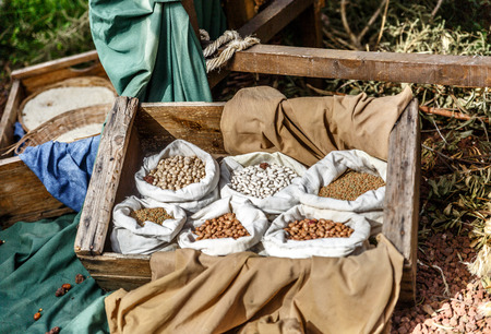 Beans of different types in small sacks in a wooden box, ready for sale