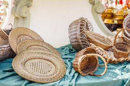 Diferentes platos y cestas de mimbre, sobre una mesa en un mercado vintaje Foto de archivo - 86787706