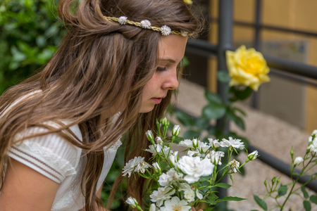 religious clothing: Beautiful girl picks some flowers in a garden on the day of her holy communion Stock Photo