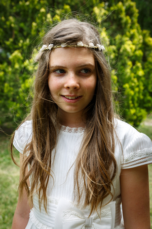 Portrait of a pretty girl with a white wreath and white costume, the day of her communion